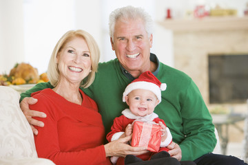 Grandparents With Baby In Santa Outfit