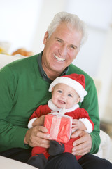 Grandfather With Baby In Santa Outfit