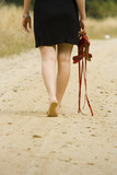 Portrait of a barefoot woman holding her red sandals poster