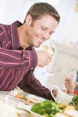 Man Drinking Wine At Christmas Dinner