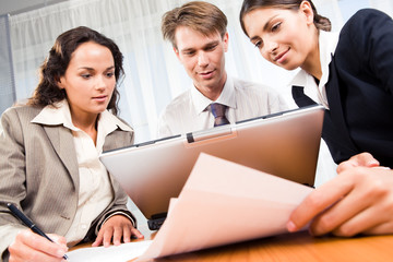 Portrait of three people looking at laptop monitor