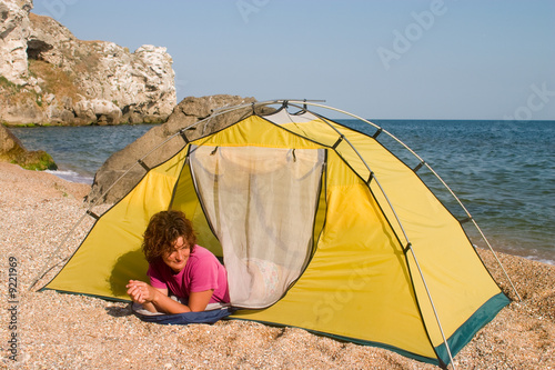 Red-haired girl lying in sleeping-bag at seaside