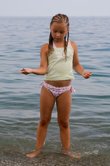 little girl stands in water ashore