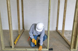 Carpenter fixing a timber framework into a concrete floor poster