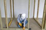 Carpenter fixing a timber framework into a concrete floor poster