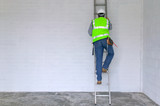 Workman in reflective vest and hard hat climbing a ladder poster