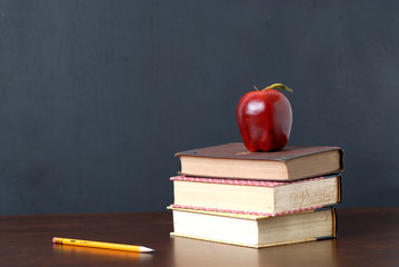 red apple and text books on teacher desk