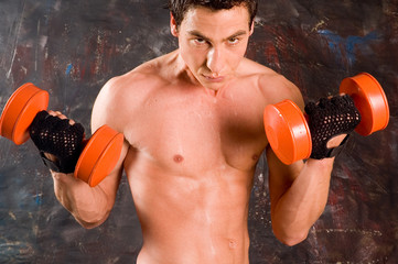 Sweaty bodybuilder training with dumbbell