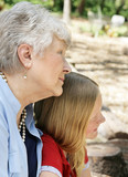 Profile of grandmother in the park with her granddaughter. poster
