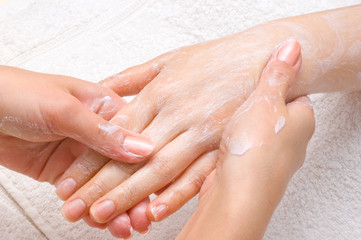 applying peeling scrub or moisturizing cream onto the hands