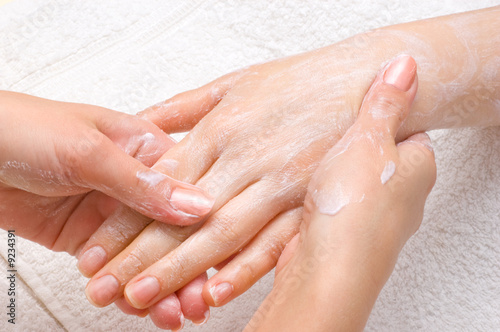 applying peeling scrub or moisturizing cream onto the hands - 9234391