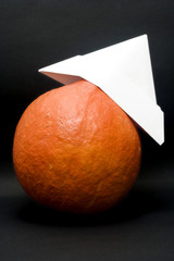 an orange pumpkin wearing a funny, paper hat