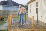 Contractor pressure washing deck , getting home ready to sell poster