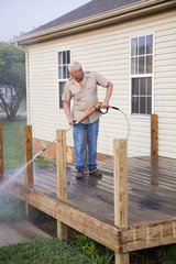Contractor pressure washing deck , getting home ready to sell