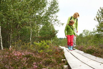 Mother and daughter walking on  plank-way in forest
