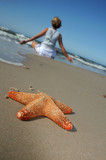 Starfish and tranquil woman on sandy beach poster