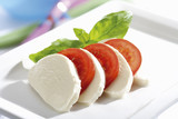 Mozzarella cheese with tomatoes and basil, close-up