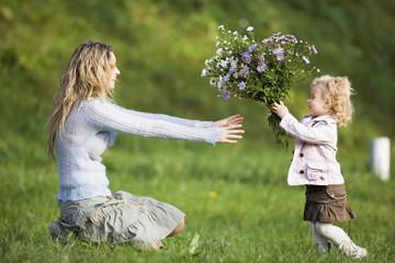 Tochter geben Mutter Blumenstrauß, Seitenansicht