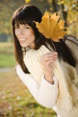 Brunette junge Frau spielt mit Herbstlaub