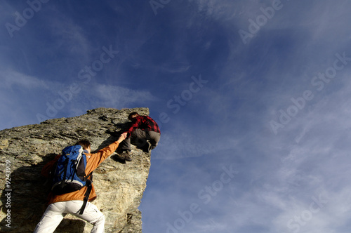 Young couple climbing on mountain peak, man helping woman, rear view