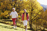 Germany, Bavaria, senior couple Nordic walking, smiling