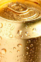 Gold can of drink with water drops close-up