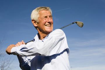 Senior Mann Golfschläger schwingen, lächeln, close-up