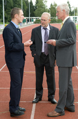 Businessmen discussing their business on a race track.
