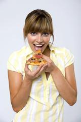 Frau jung essen Stück Pizza, lächeln