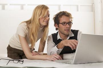 Junger Mann und Frau mit Laptop, lächeln