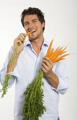 Junger Mann essen Karotten