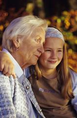 Enkelin und Großmutter Oma umarmen, lächeln