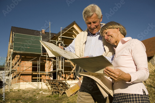 Senior couple looking at blueprints in front of incomplete built house, smiling
