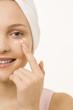Portrait einer jungen Frau, Gesichtscreme unter Augen