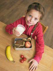 Mädchen mit Glas Milch und Lunchpaket Schreibtisch,