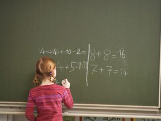 Mädchen schreiben auf Tafel, Rückansicht