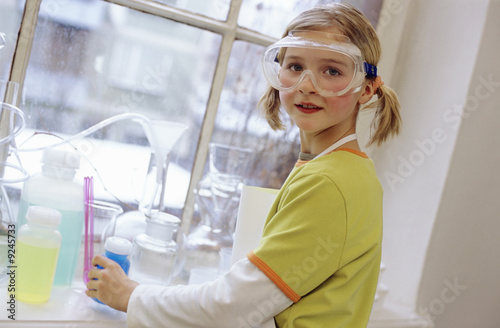 Girl (8-9) in chemical lab wearing protective goggles, portrait