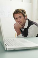 Junger Mann sitzen mit Laptop, Portrait