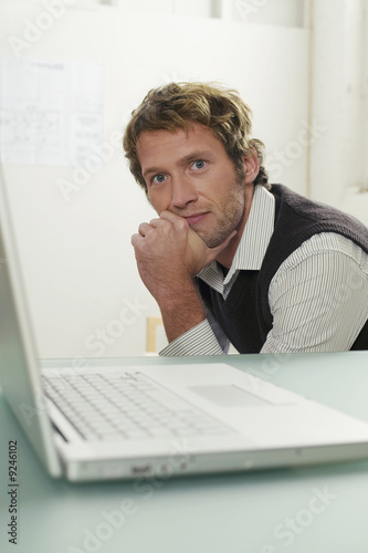 Young man sitting by laptop, portrait
