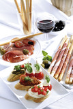 Grissini with parma ham and olives and mozzarella with tomatoes, italian starters
