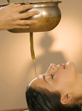 Young woman in spa with oil being poured on forehead, eyes closed