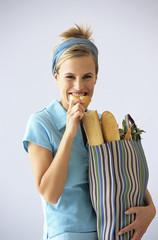 Frau mit Einkaufstüte, essen Baguette