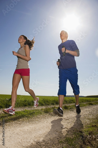 Young couple jogging, man carrying dumbbells