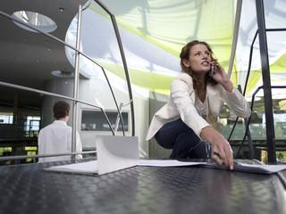 Junge Unternehmerin Geschäftsfrau mit Mobiltelefon, fallen Papiere auf dem Boden
