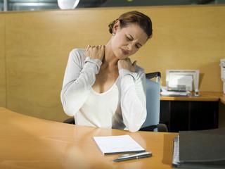 Frau sitzen am Schreibtisch Stretching, Hände auf die Schulter, close-up