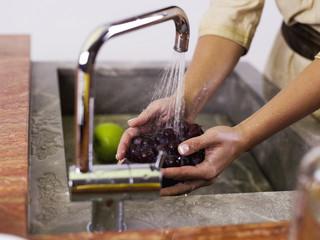 Frau waschen Trauben Küchenspüle,
