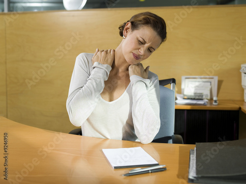 Mid adult woman sitting at desk stretching, hands on shoulder, close-up