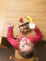 Mädchen mit Lunchpaket auf dem Schreibtisch, Glas Milch, Draufsicht, Portrait
