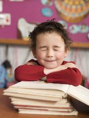 Junge sitzen am Schreibtisch und stützen sich auf Stapel der Bücher, die Augen geschlossen, close-up