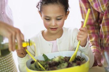 Eltern mit Tochter bereitet Salat